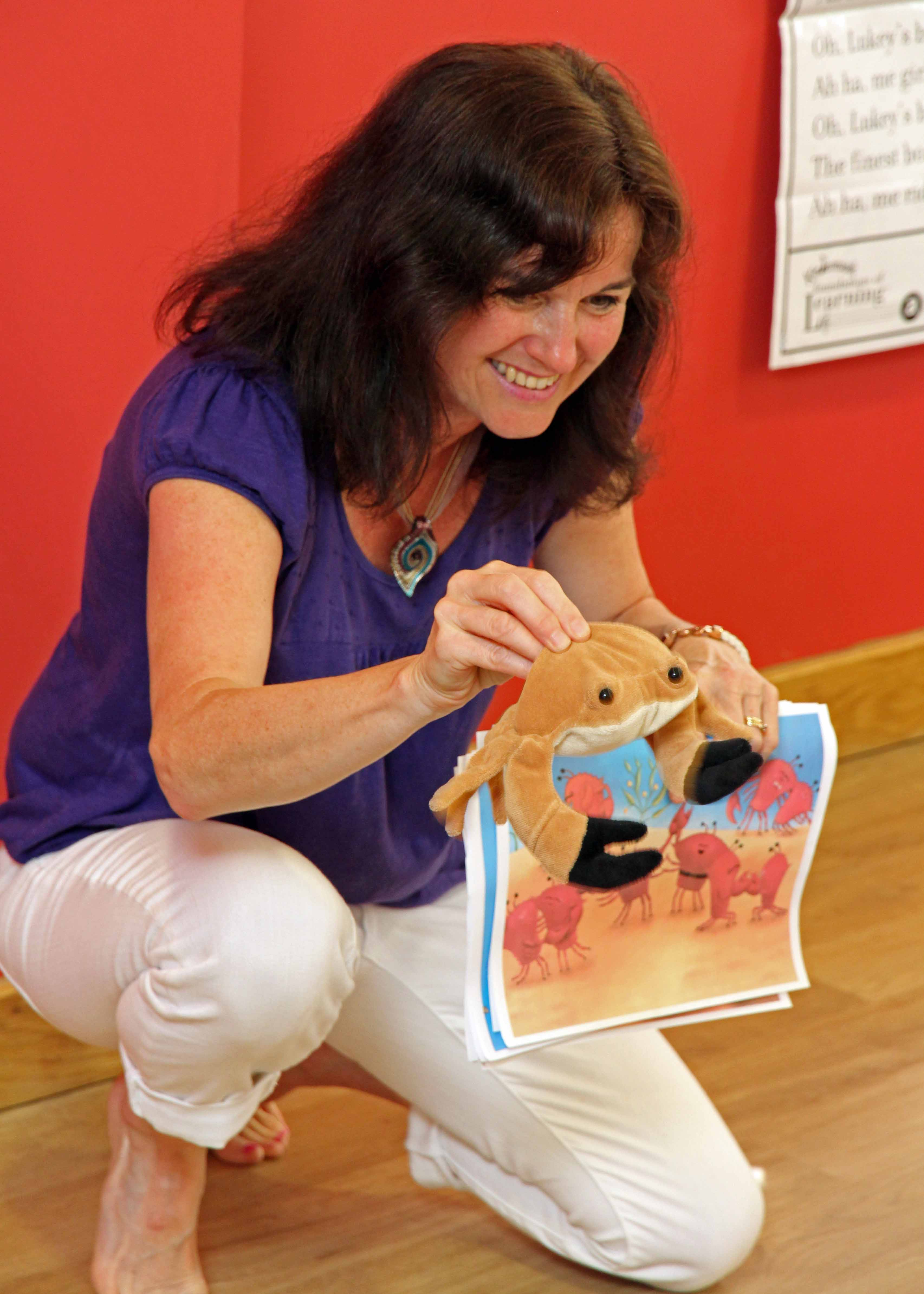 Image of Jan Holt the Kindermusik By Jan teacher smiling and kneeling down showing the children in her class a picture of crabs playing and a soft toy crab too.
