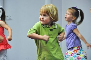 A preschool boy in a green t-shirt dancing at one of his preschool music classes with two girls running around behind him.
