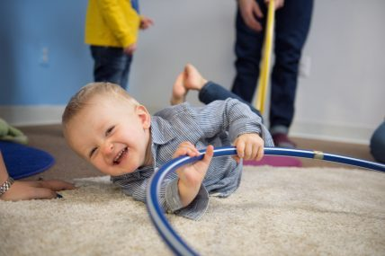 A two year old boy in a striped shirt rolling around on the floor, laughing, playing with his hula hoop at his Kindermusik toddler music class in Burgess HIll.